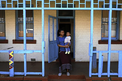 Yonela Mkalipi and her son, Omphile Makubung, outside their home in Crown Mines village.