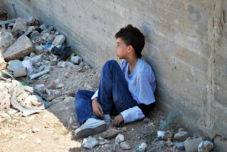 Photo: A child sitting on the floor in Bil'in, West Bank