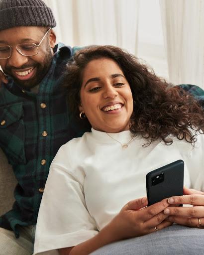 Un uomo e una donna sono seduti e la donna sta usando il suo telefono.