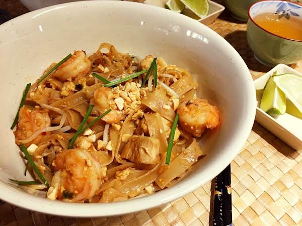 Pad Thai Noodles With Chicken And Shrimp On A Beige Table Mat With Chop Sticks, Lime Wedges And A Cup Of Green Tea.