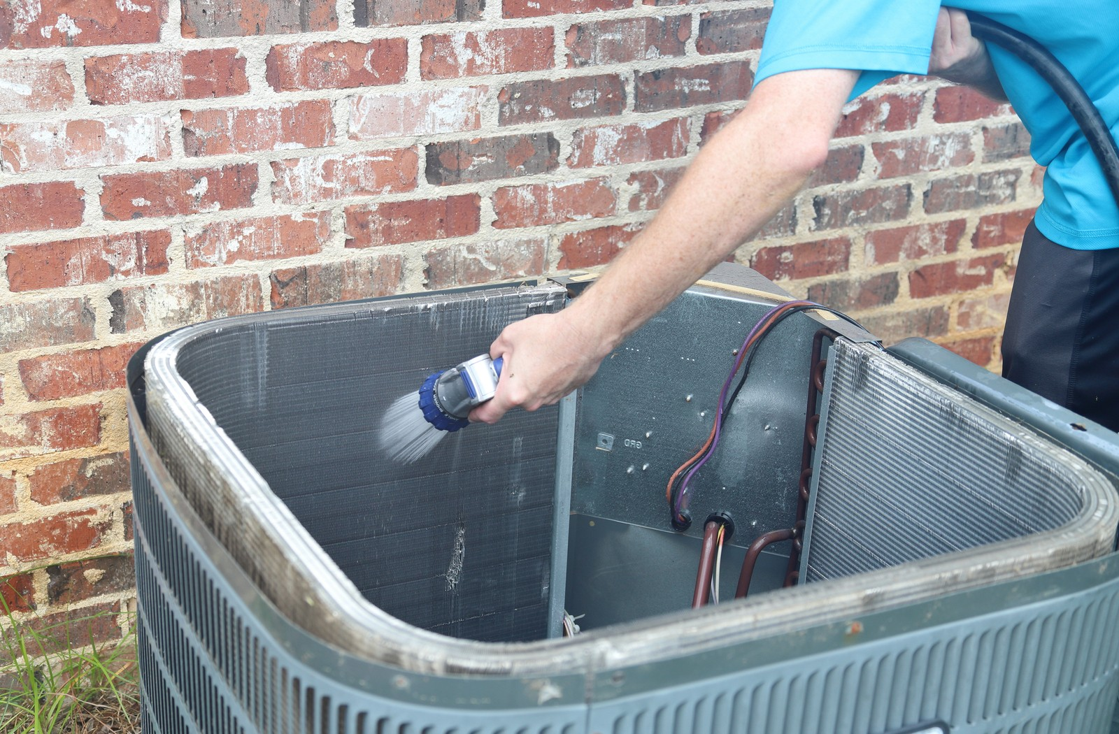 Man using a garden hose to clean air conditioner coils
