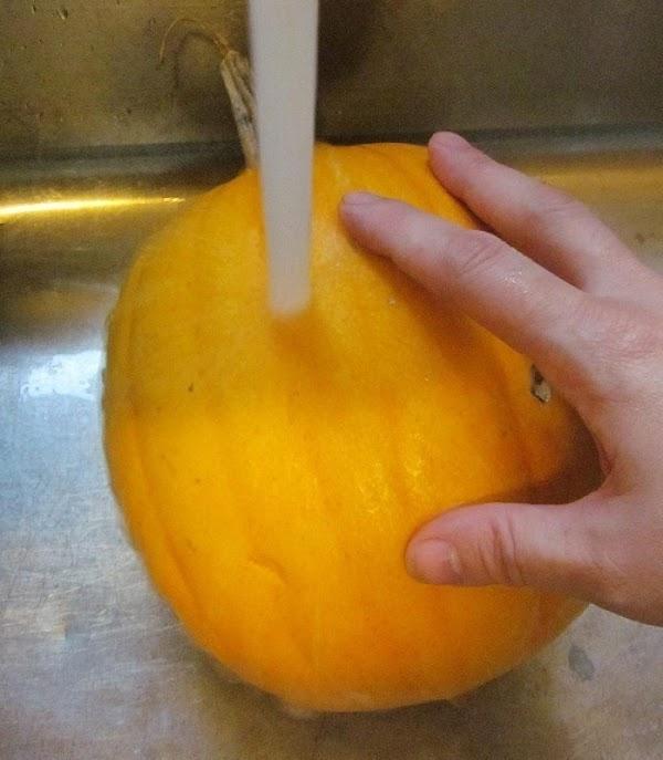 Wash the pumpkin under a cool tap. Then, cut your pumpkin in half.
