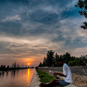 Awareness at Sunset by Shikhar Sharma - People Portraits of Men ( reading, sunset, man, river, newspaper, bicycle )