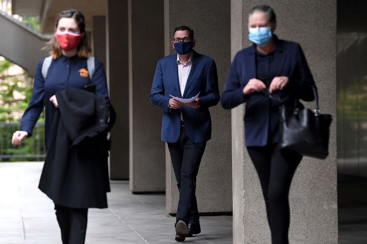 Victorian Premier Daniel Andrews (C) arrives to a press conference wearing a mask as the state of Victoria reacts to an outbreak of the coronavirus disease (COVID-19), in Melbourne, Australia, July 20, 2020.