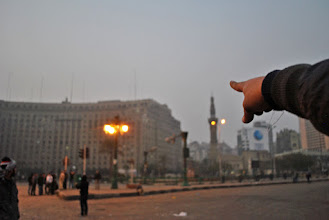 Photo: A man points in the direction of an army sniper spotted atop the 'Mugama' government building in Tahrir Square. At least two rounds of sniper fire were heard during the early morning attack.