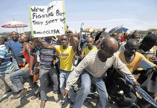 WANTING MORE: Striking platinum miners march near the Anglo-American Platinum mine near Rustenburg, North West Province, on Friday. Amplats fired 12000 workers on the same day, and said 5000 were not likely to be rehired