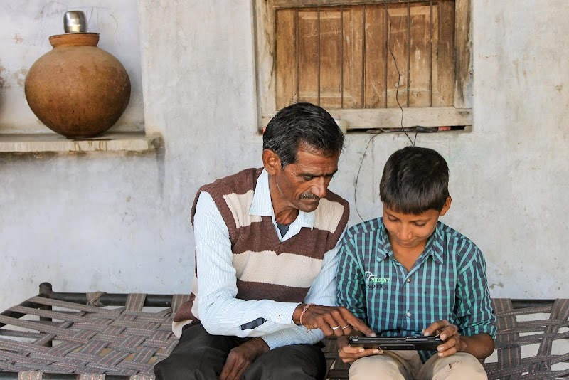 Young boy in plaid shirt looking at tablet and getting assistance from man in striped vest seated to his right.