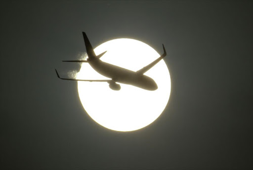 An aircraft is silhouetted by the sun