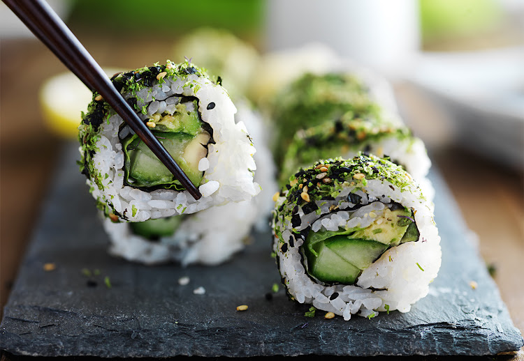 Green eating: kale and avocado sushi roll with chopsticks