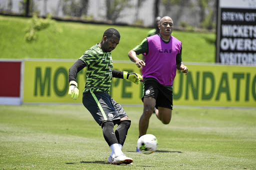 Itumeleng Khune perfects his kicking skills while Dino Ndlovu watches on during yesterday's session at Steyn City. /Lefty Shivambu/ Gallo Images