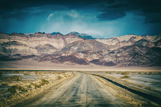 Photo: Down This Old Road  Picture the scene... it's 1975, I'm riding my motorcycle through Death Valley and I pull out my Nikon FT2 to capture the road I'm traveling.  To the right is nothing. To the left is nothing. The clouds are rolling in like there's a storm approaching but there's no wind to speak of. There is stillness and quiet. The brown in the hills is like a lifeless form with no voice. I am alone. I ride on. It's not the destination I seek, only the journey.  /<scene>  So, fantasy aside, with the announcement by +Brian Matiashof the release of Niks Analog Efex Pro v2 I had to have some play time with the new features. This image wasn't taken in 1975, nor was it taken with a FT2, it was taken last year with my digital Nikon D300s. Yes, it is in Death Valley, which is the most truth in my little fiction above. But I wanted to create a filmish look to the image.  Most of the time when I process an image I'm looking to convey the truth of the scene; in other words, I want you to see what I saw. For this little experiment I played with the settings to give the image a vintage feel. So although you are seeing what I saw as the scene goes, I wanted you and I to be able to see it as it might have been seen some 40 plus years ago by a hippie vagabond with no destination in mind.  Buy a print at:http://bit.ly/1k3GUUn  #desert  #analogefexpro  #deathvalley