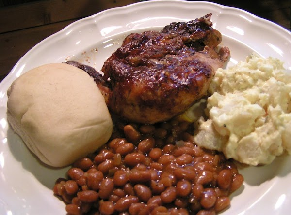 A plate of baked beans, potato salad, a biscuit, and barbecue chicken.