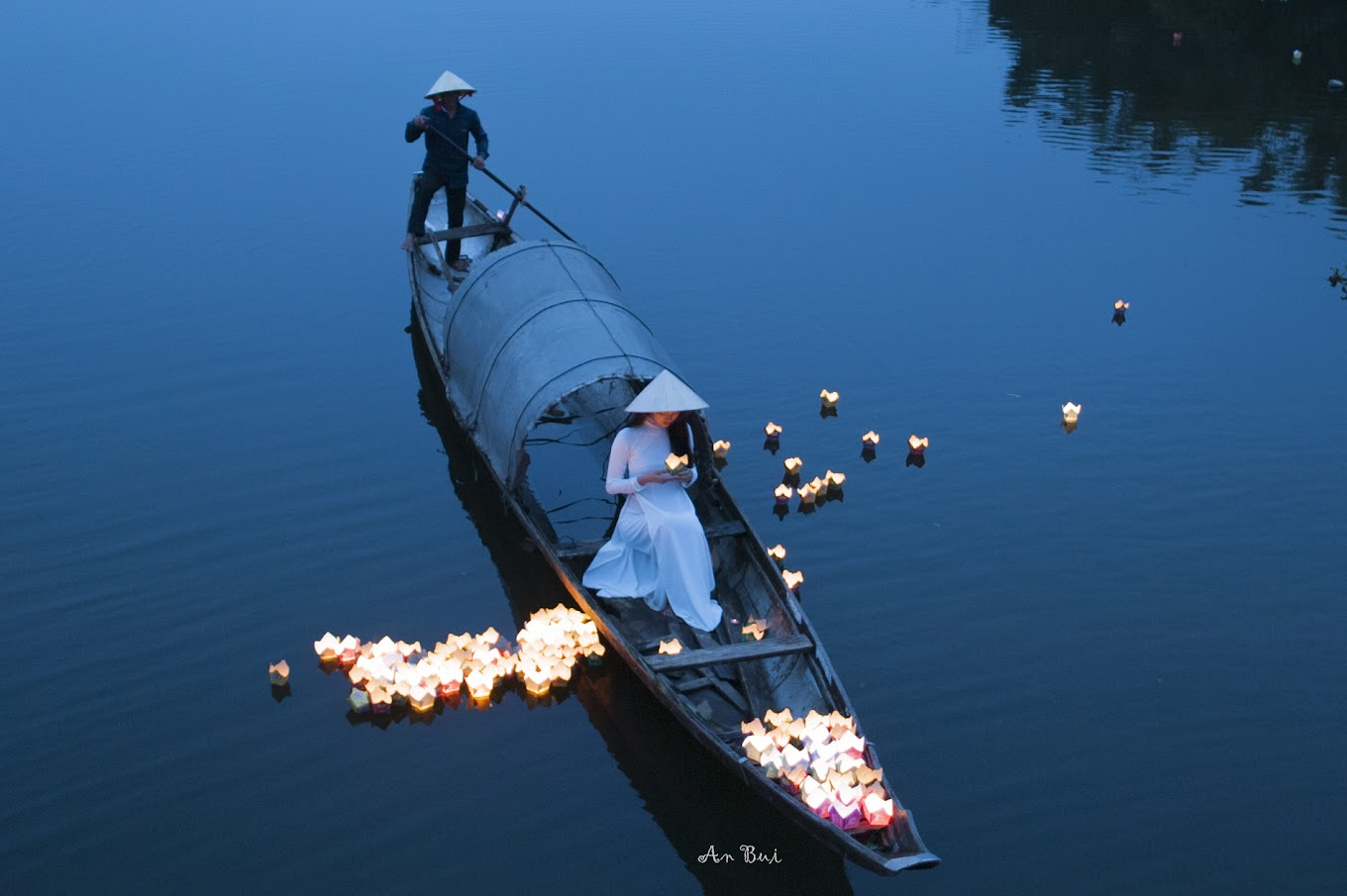 Floating red lantern with Ao Dai in the river