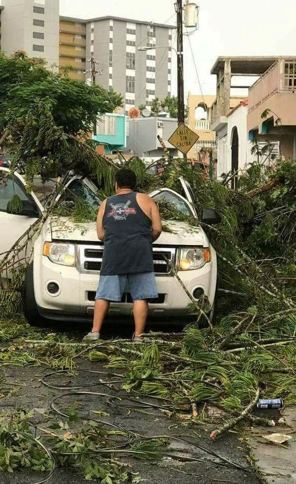 A man removes debris from a car following high winds as Hurricane Irma nears San Juan, Puerto Rico, on Wednesday. Picture: REUTERS