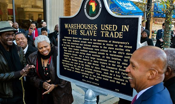 A group gathers around a plaque on a city street. The plaque describes how warehouses in the area were historically used in the slave trade.
