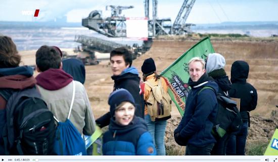 Menschengruppe vor Tagebau.