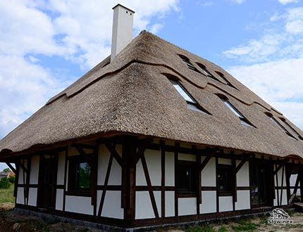 Dom z muru pruskiego z czarmymi belkami i trzcinowym dachem