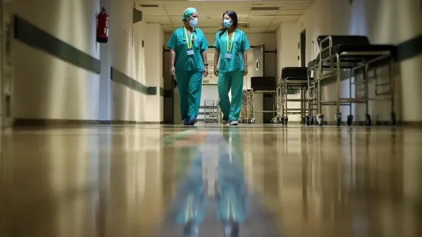 Dos sanitarios recorren un pasillo.