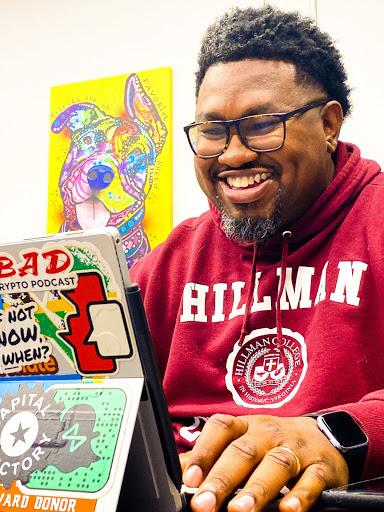 Man working on his laptop, smiling.