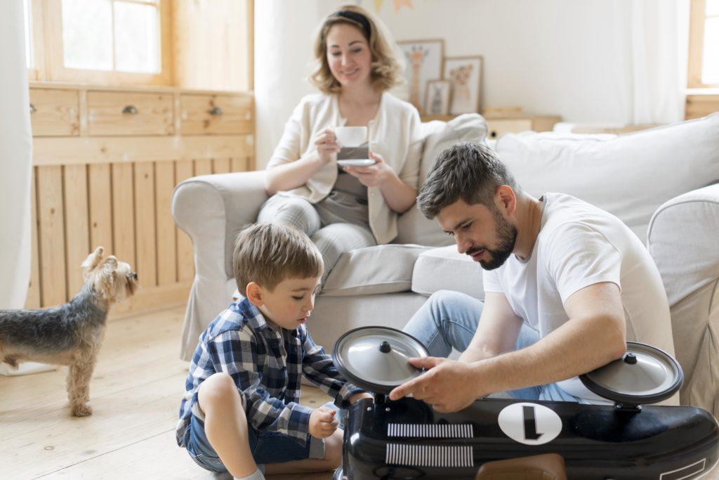 un homme et son fils en train de jouer sur une roue d'un véhicule miniature et une femme assise sur un canapé blanc en arrière dans une maison de montréal
