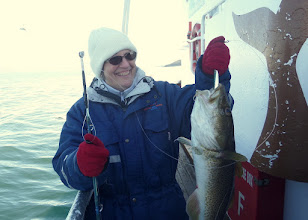 Photo: On the way back to the dock some of the people fished for cod.  This is Karen and her catch.  It was cold and we were all issued a full length, heavily padded jumpsuit.
