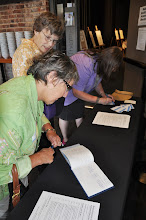 Photo: Angela Terry, Marilyn Sandall, and Carmen Sterba signing in and picking up copies of the day's schedule.