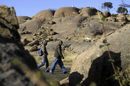Reparations process: Workers walk past a memorial to striking miners killed during clashes with police near Lonmin's Marikana mine in 2012. Families of the dead are still awaiting compensation. Picture: REUTERS