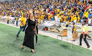Kaizer Chiefs marketing boss Jessica Motaung waves to the supporters after a match against Highlands Park in Johannesburg. Behind her is younger sister Kemiso Motaung.