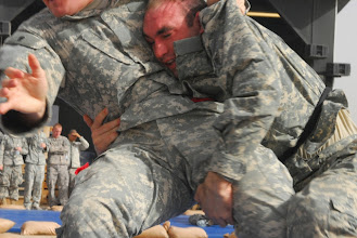 Photo: Soldiers take their grappling down from standing level to ground-fighting during the All Iraq Combatives Tournament at Camp Bucca, Dec. 19. Teams from all parts of Multi-National Division South converged on the camp to take part in the grappling tournament.