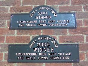Photo: Consecutive Small Market Town awards, on the side of the library.