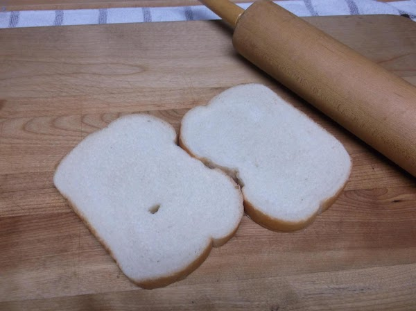 Using a rolling pin, flatten 7 or 8 slices bread.