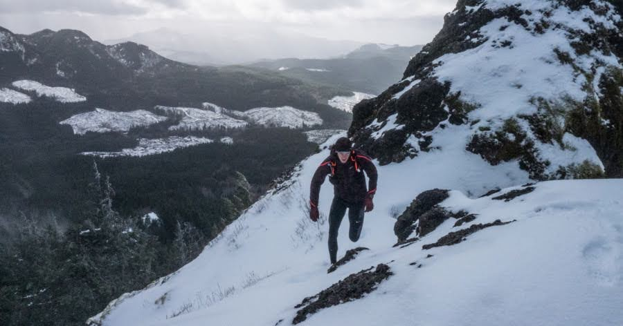 A photograph of endurance sports coach Ian Hosek running up a mountain trail