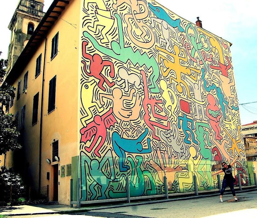 un murales di Keith Haring, una intera parete, in basso è protetto da un vetro antiproiettile descrizione in basso