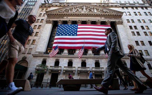 Pedestrians walk past an American flag displayed outside of the New York Stock Exchange in New York, the US, on Monday. Picture: BLOOMBERG/MICHAEL NAGLE