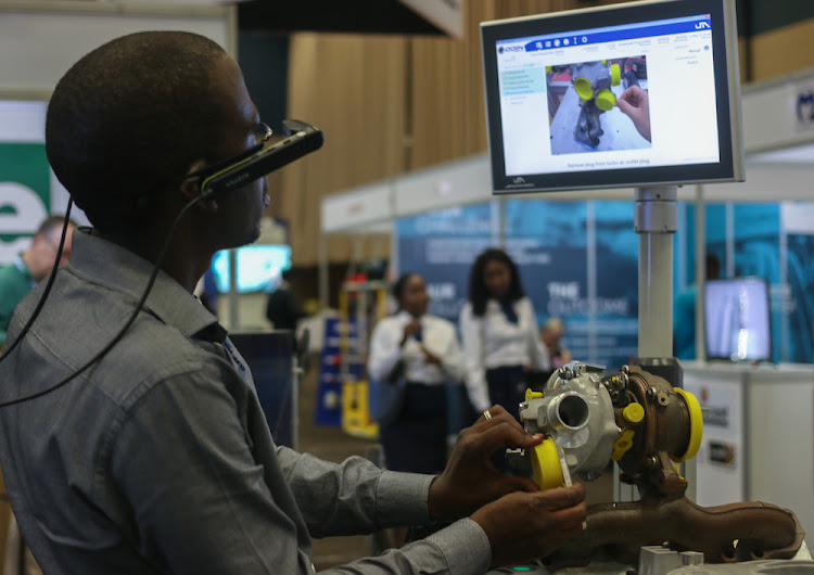 A trade show visitor tries his hand at component assembly using Jendamark's operator guidance system.