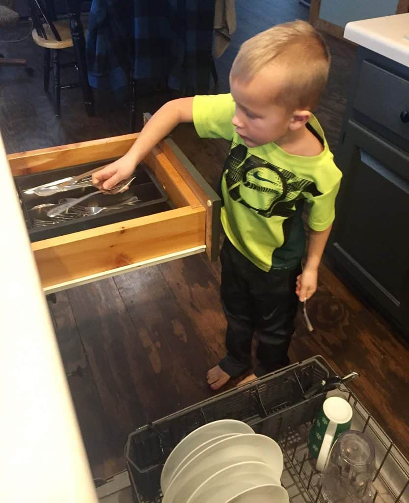 Age Appropriate Chores for preschoolers: A photo of a preschooler putting silverware away.