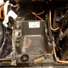 Photo: Wichtig: Erst die Spannfeder aushängen (unten), dann den Motor. Motor-»Wanne« (Marcegaglia), mit Flusen