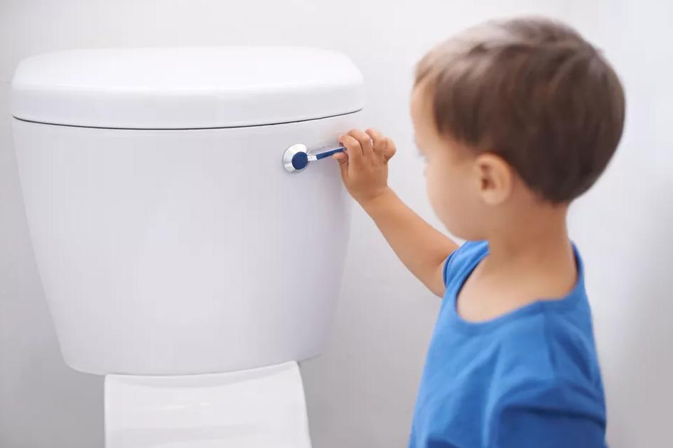Uma criança apertando a descarga do banheiro.
