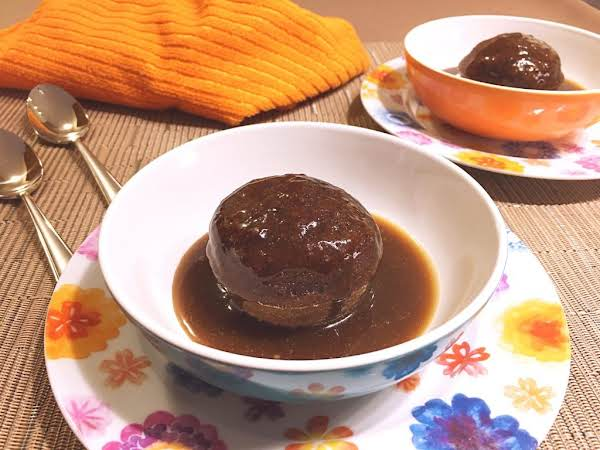 Pudding In A Bowl Topped With A Brown Sauce.
