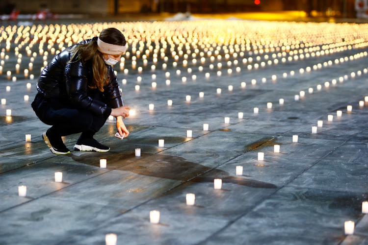 A woman lights candles symbolising the Covid-19 victims during a candlelight vigil in front of the seat of the Swiss federal parliament, Bundeshaus, in Bern, Switzerland. Picture: REUTERS/Arnd Wiegmann