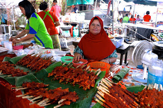 "Photo: a vendor selling ""gkai gkaw lae"" – a southern-style grilled chicken on skewers that has been marinated and basted with a sweet curry sauce – at Nakhon Sunday market"