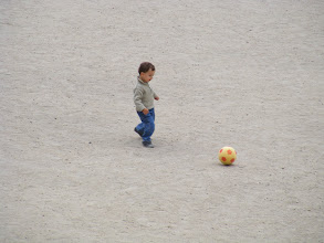 Photo: This small boy is getting an early start on football with his grandfather, and he enthusiastically chases the ball around for some time.