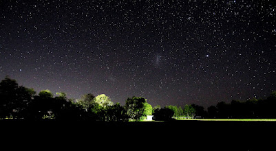 "Photo: I took this south-facing, wide-angle, image, from the Macarthur Astronomical ""dark sky"" site at The Oaks, NSW last week. The observing field is behind a sportsground and unfortunately the local rugby team had a game on. The floodlights are 200m behind the camera but clearly illuminated the trees 100m ahead of the camera!  Despite this, the Large and Small Magellanic Clouds are easily visible. The brightest star is Canopus.  30 seconds at ISO 2000, f/3.5, focal length: 10 mm, FOV: 108deg (diag)."