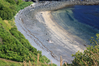 Photo: A couple sun bathing on a beach in Kodiak
