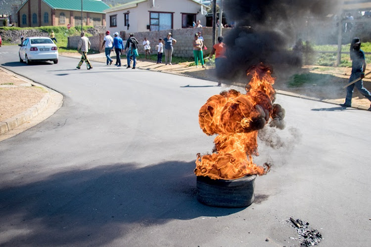 Burning tyres lined the main road of Kleinmond during a protest against municipal cleaning tenders.