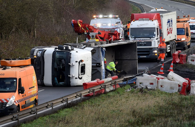 Rescuers work on the A2 motorway in Marly, northern France, after a truck was tipped over in the early morning from strong winds brought by storm Ciara on February 10, 2020. - Hundreds of flights and train services were cancelled on February 10 as Storm Ciara sweeps over northwest Europe packing powerful winds, and leaving swatches of Europe without power after unleashing torrential rain and causing flash flooding.