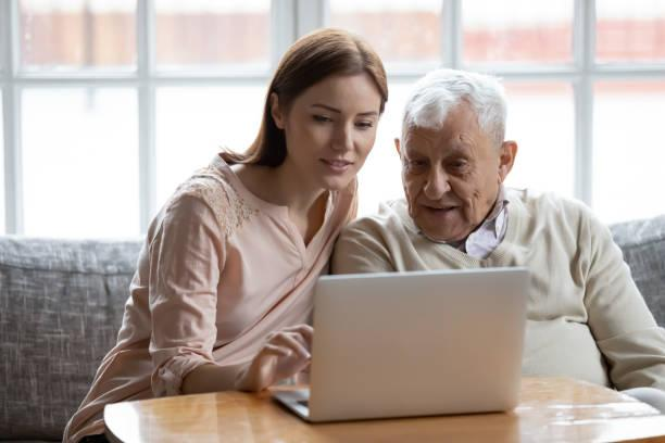 Adult daughter old father choose services via internet using computer Grown-up daughter and old 80s father choose goods or services via internet or web surfing together at home. Younger generation caring about older relatives teaching using computer useful apps concept YOUNG PEPLE HELPING OLDER PEOPLE stock pictures, royalty-free photos & images