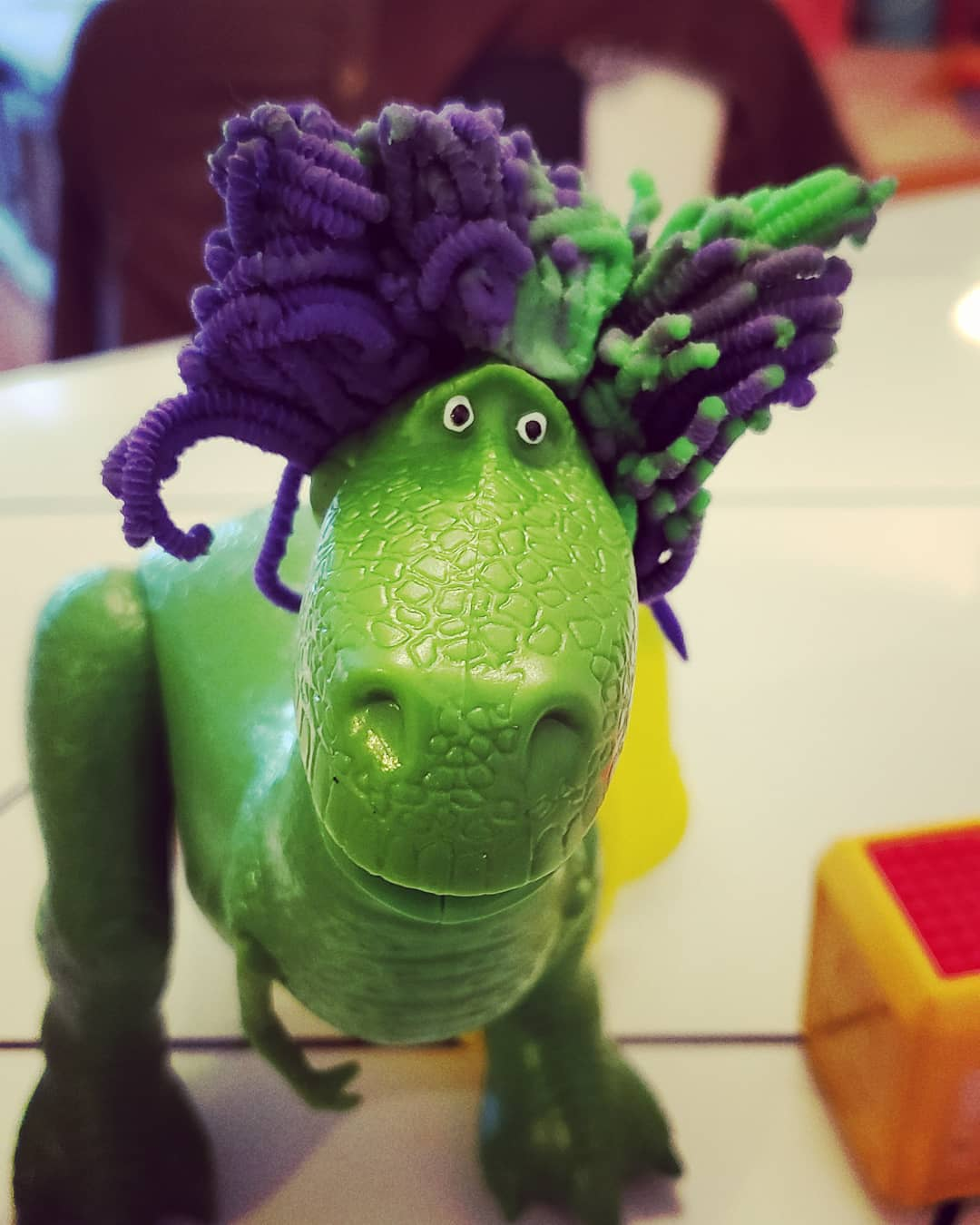 Image description: A Rex dinosaur with a bunch of purple and green Playdough tat looks like hair.