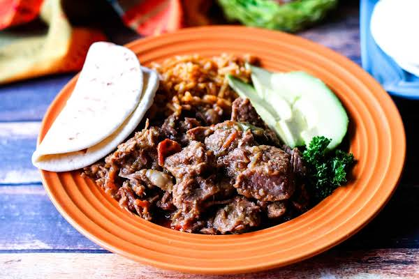 A Bowl Of Carne Guisada With Mexican Rice And A Tortilla.