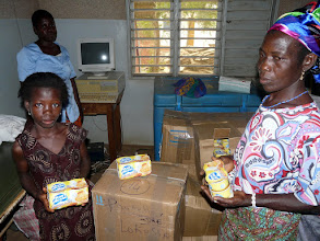 Photo: Paulette reçoit ses cartons de friperies et boîtes de riz au lait
